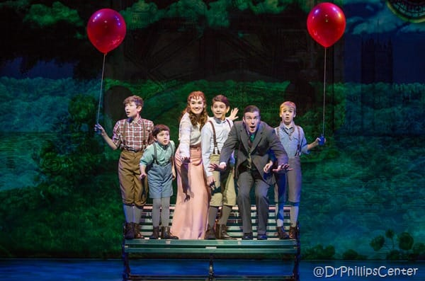 A small cast from Finding Neverland standing on a bench in a park setting
