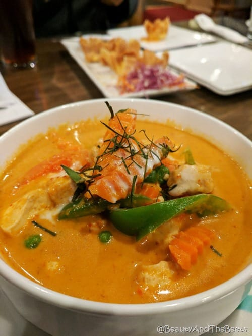 a white bowl filled with a yellow curry sauce with a garnish of carrots and green vegetables
