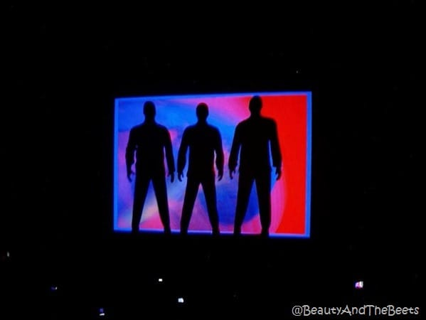 3 shadows in fromt of a red blue and purple LED screen on a black background