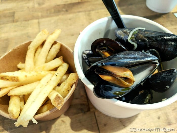 a cup of golden french fries next to a cup a white cup filled with a pile of black mussels on a wooden table