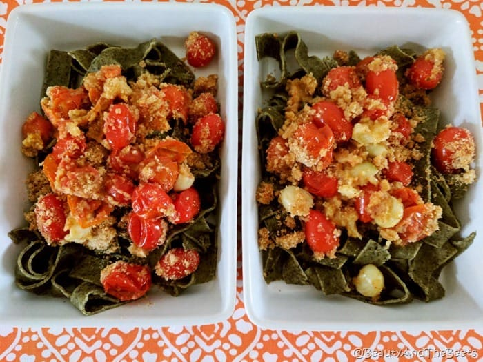2 rectangular white dishes filled with spinach pasta, roasted tomatoes, garlic and breadcrumbs on an orange placemat