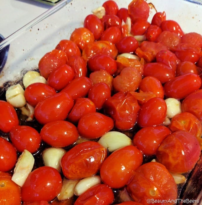 a glass casserole dish filled with blistered tomatoes and garlic