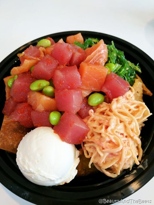 a black bowl filled with raw tuna and salmon with krab salad, edamame, a scoop of cream cheese on a white background