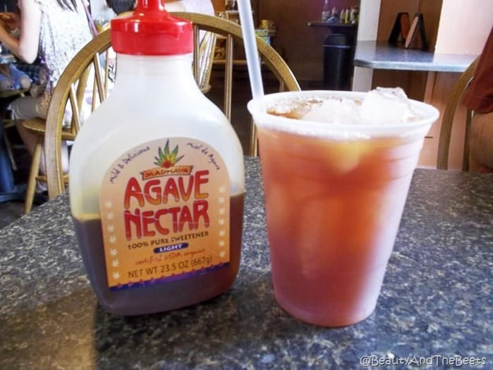 a plastic cup of iced tea next to a bottle of Agave Nectar on a gray marble table