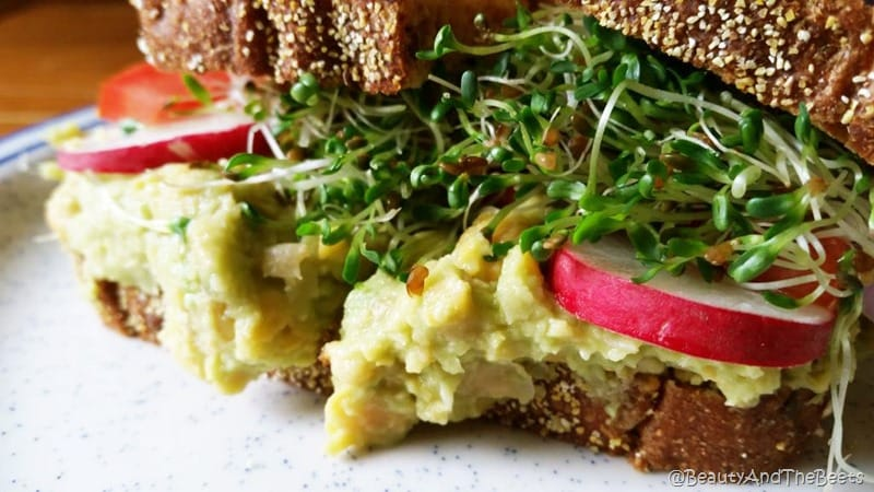 a spread of chickpea avocado mash with radish and toasted wheat bread on a white speckled plate