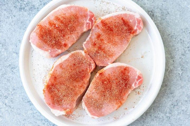 4 raw boneless pork chops covered in seasoning