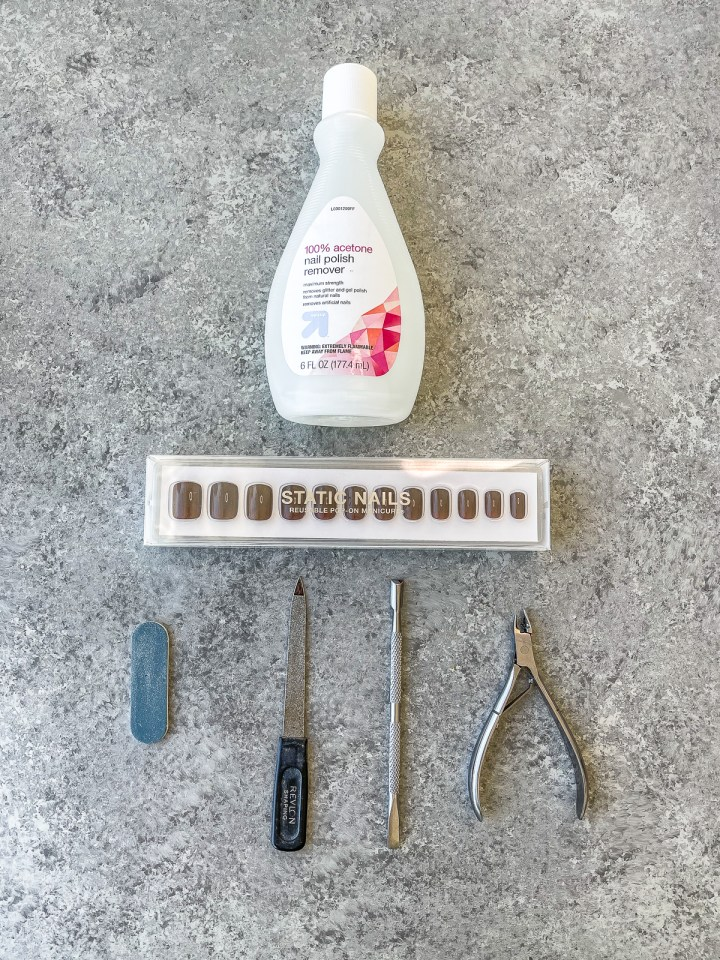 press on nails, file, cuticle stick, nail clippers and nail polish remover laid out