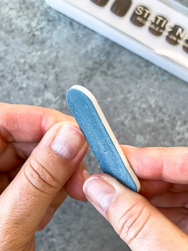 filing nails with a small blue nail file