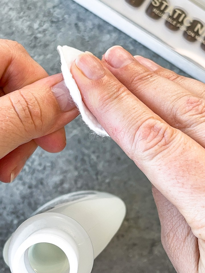 wiping nail beds clean with nail polish remover