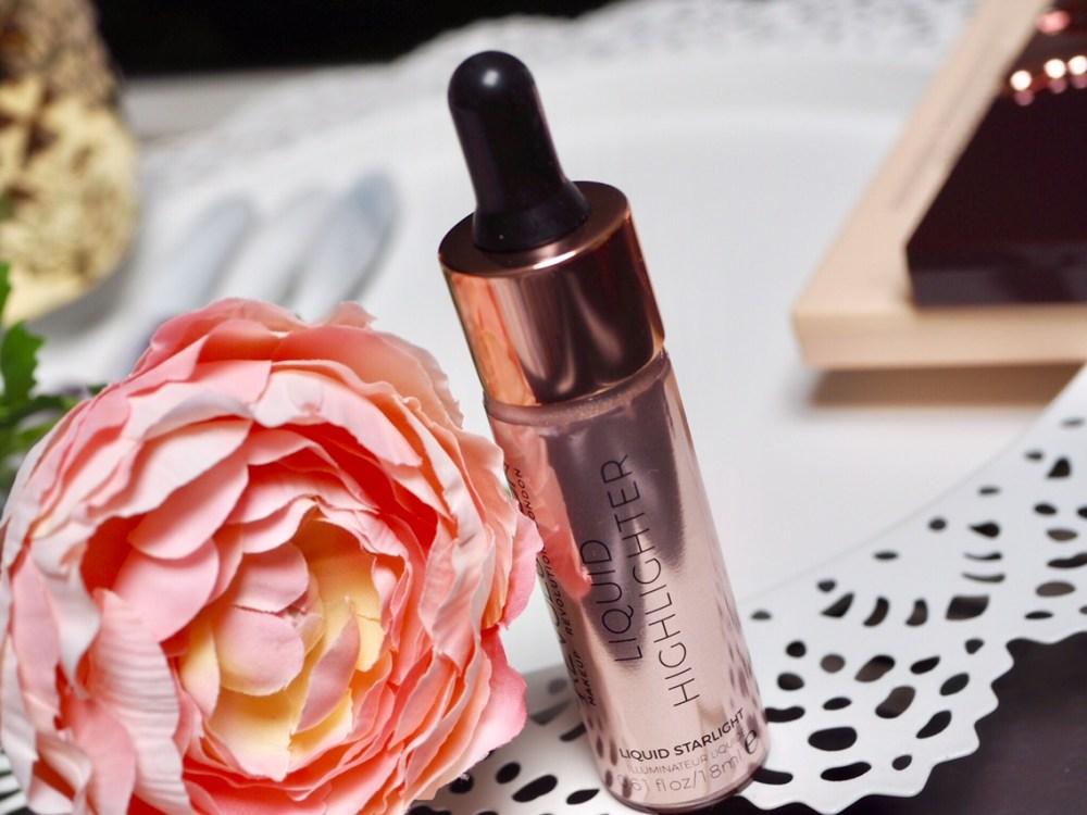 Makeup Revolution Liquid Highlighter Review- pretty gold metallic dropper bottle next to a flower