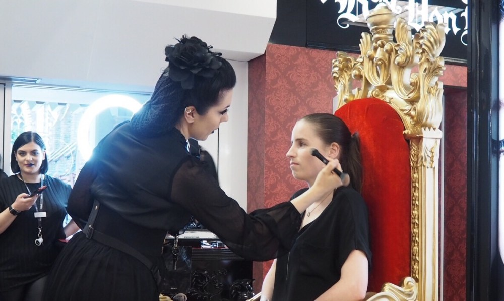 Lady having her makeup done on a gold throne