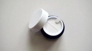 Holding the Malin + Goetz Revitalizing Eye Cream with the safety cap on
