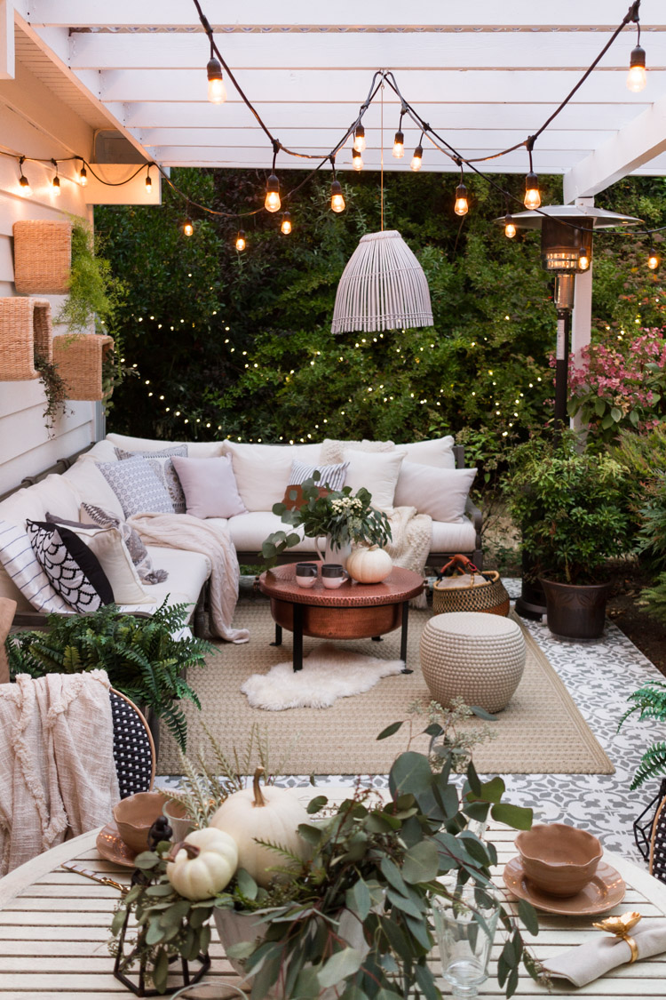 An outdoor patio with lots of textiles and lighting.