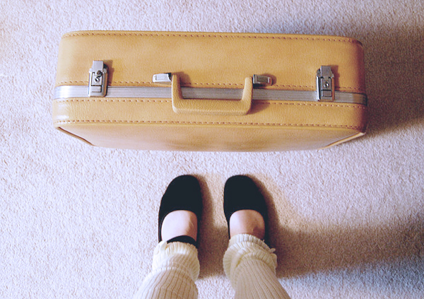 Image of a woman's feet and a suitcase