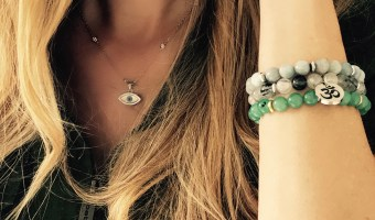 Saarah wassel samadani with awaken the peace bracelets stacked on her wrist showing her arm, lower half of face, an evil eye necklace wearing a green top