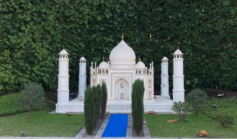 taj mahal lego model at legoland california with green bushes behind it