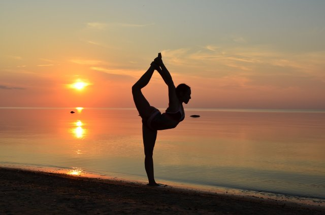 beach yoga pose in sand at sunset 1