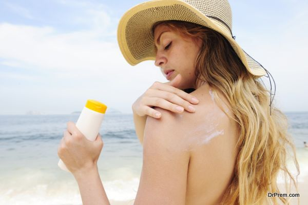 woman applying suntan lotion at the beach smiling