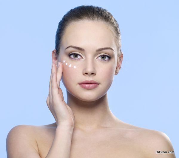 girl applying cream on her  skin around eyes