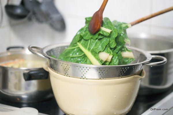Preparing healthy lunch in the kitchen, blanching chard using kitchen utensils