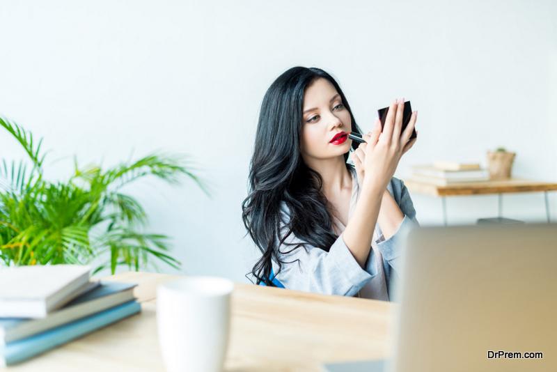 businesswoman applying lipstick at workplace