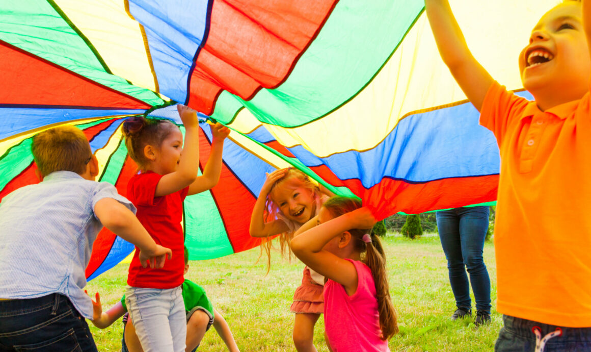 photo of children playing Jabadao under a huge rainbow cover