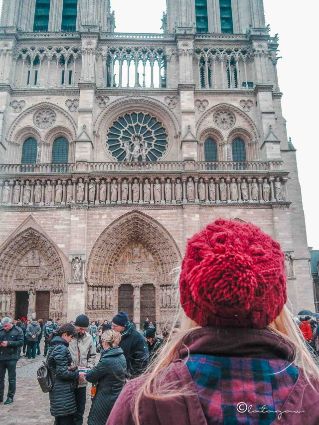 tourist taking a photo of notre dame cathedral in paris france