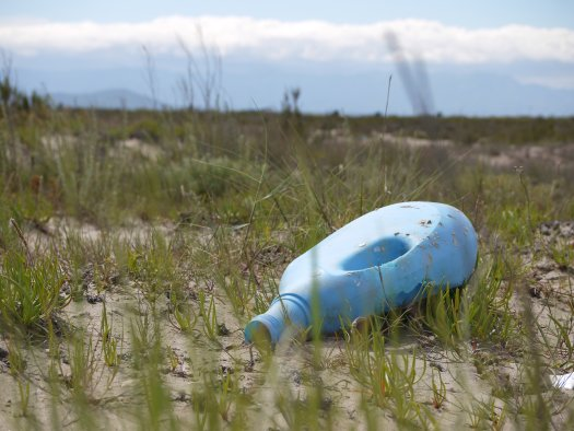 Photo of a discarded plastic laundry detergent bottle on the ground, by nicholasrobb1989 on Pixabay