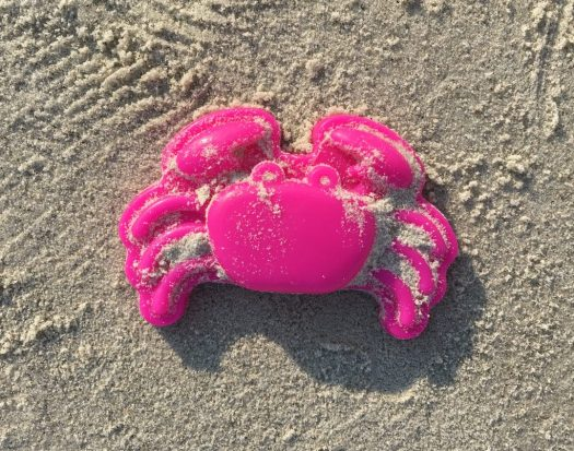 Toy pink crab sand toy.