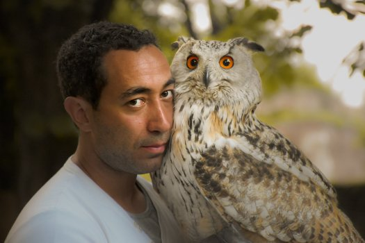 Photo of a man posing with an owl.