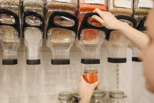 Person filling jar from bulk bins at store