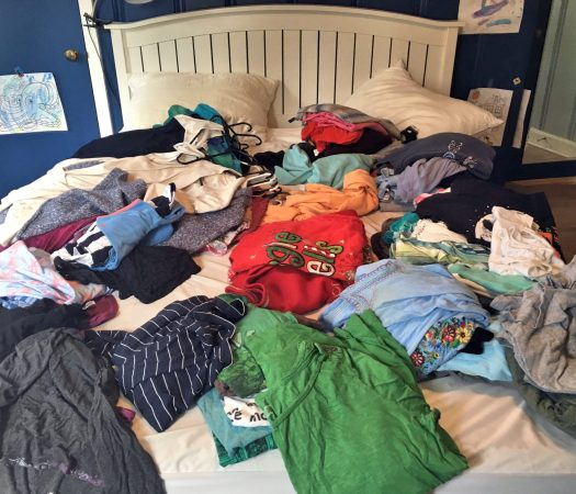 Clothing piled on bed