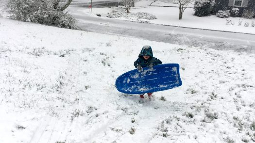 Boy with blue sled in snow
