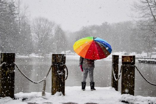 Person holding rainbow colored umbrella in front a snowy pond