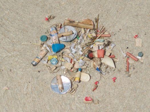 Fireworks debris piled up on sand.