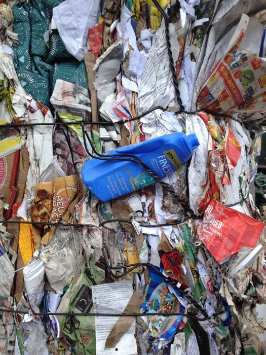 Paper recycling bale, contaminated with a blue plastic Finesse shampoo bottle.