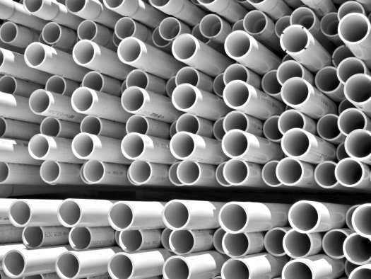 White PVC pipes stacked at a manufacturer or store.