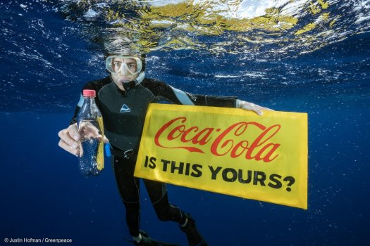 """Greenpeace scuba diver holding up a Coca-Cola bottle and sign: """"Coca-Cola is this yours?"""" Found in the Great Pacific Garbage Patch."""