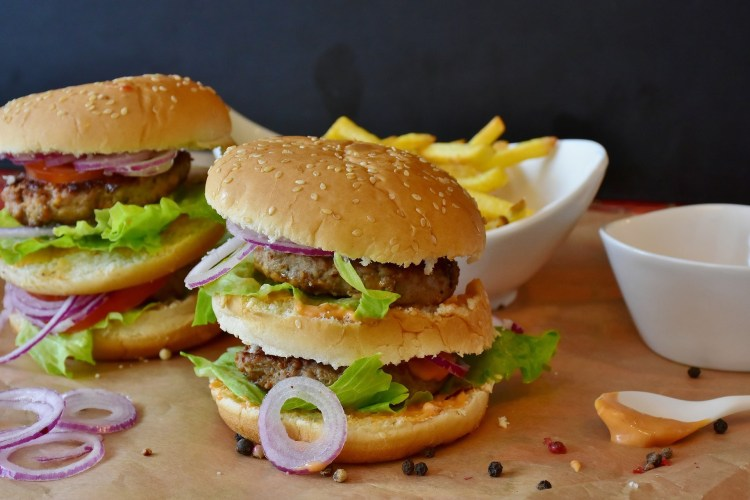 large burger and chips on a wooden surface