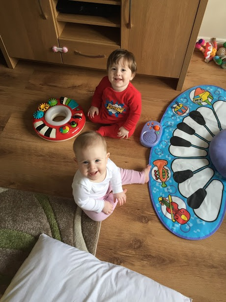 twin babies, sitting by a piano floor mat, smiling.