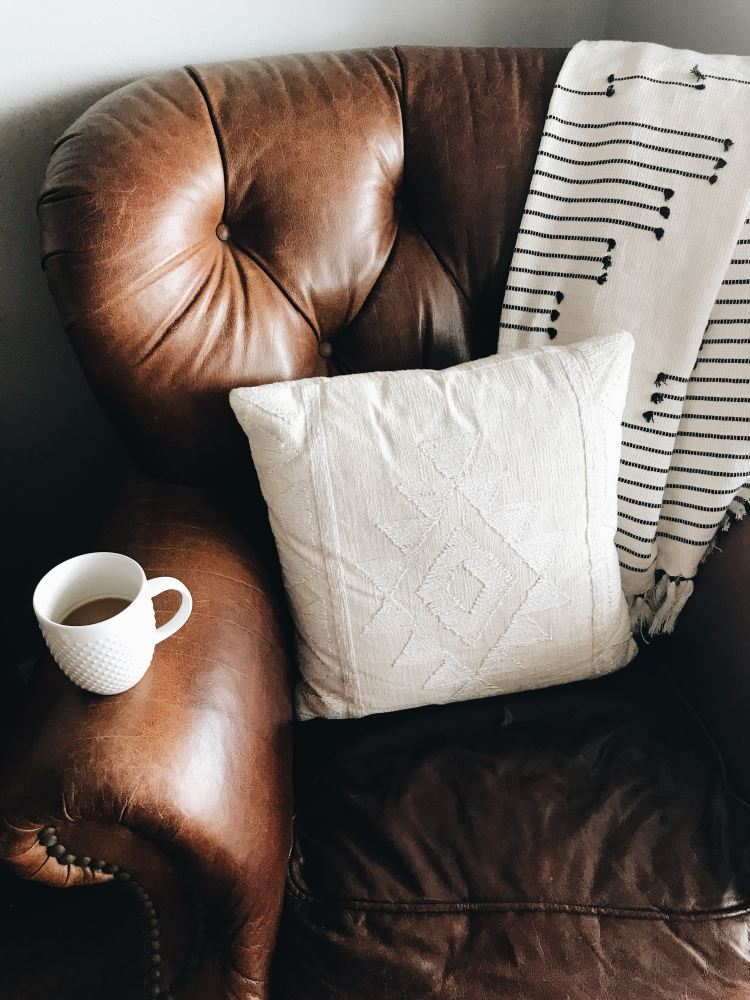 brown leather armchair with white cushion and white coffee cup