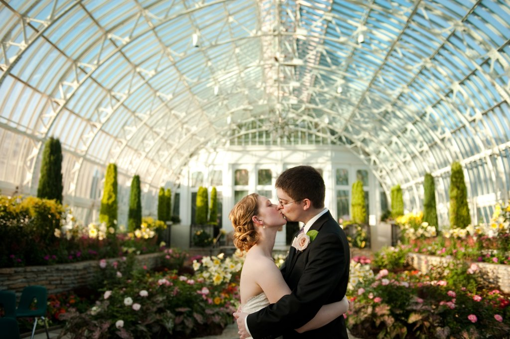 Bride and groom kiss at como conservatory wedding in st paul under the glass greenhouse roof surrounded by flowers