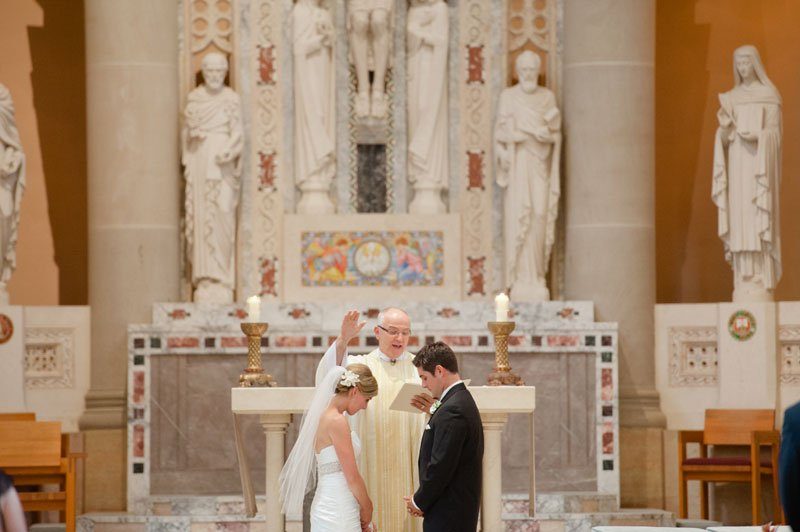 priest blesses bride and groom at St Thomas More Catholic Church in St Paul, MN
