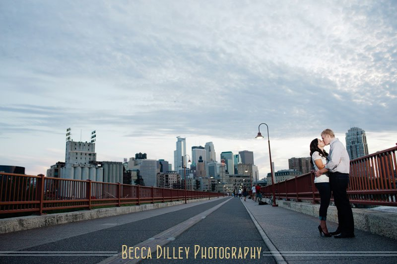 minneapolis summer engagement photos kissing on stone arch bridge
