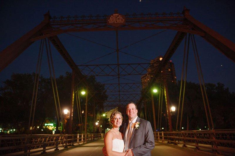 Bride and groom on Nicollet Island at night with bridge behind them Minneapolis MN