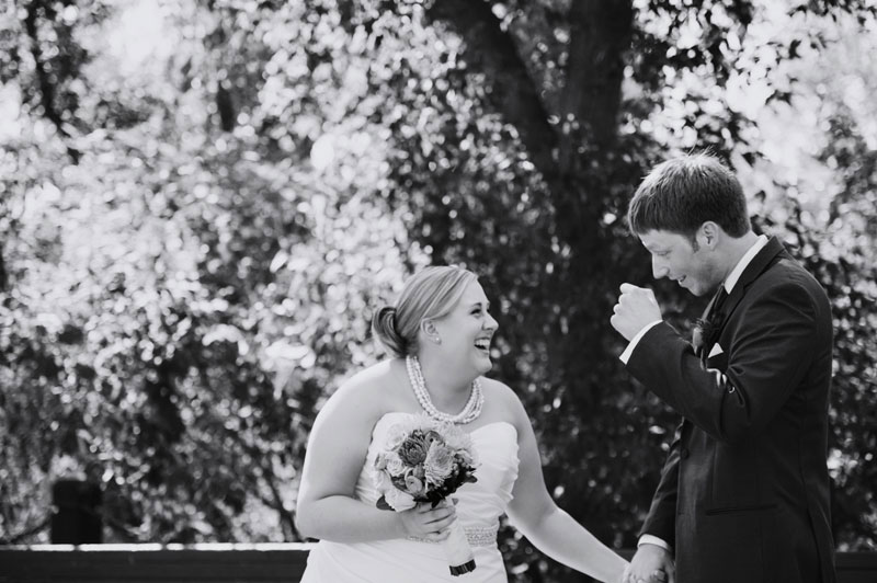 bride sees groom for first time laughtng at stone arch bridge minneapolis wedding photographer