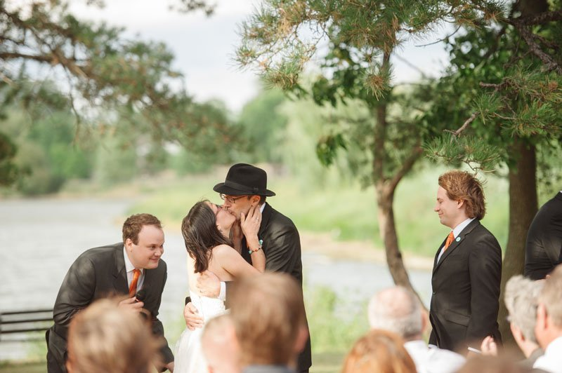 bride and groom share first kiss at ceremony on Lake Hiawatha in South Minneapolis