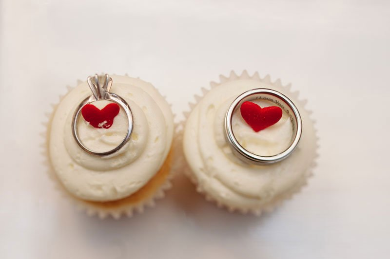minneapolis wedding photographer wedding rings on white cupcakes with red candy hearts minneapolis wedding photographer
