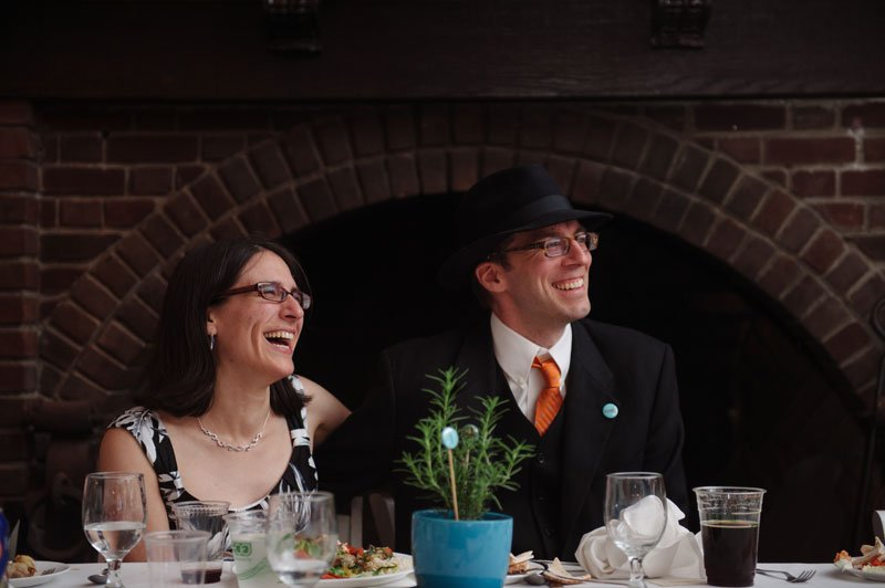 bride and groom laugh during toasts at Theadore Wirth Park Chalet Minneapolis