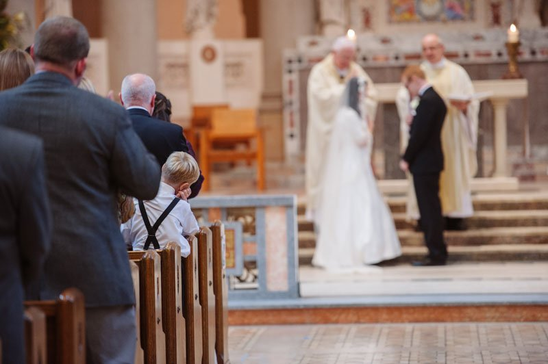 ringbearer looks on at ceremony at st thomas church wedding st paul mn